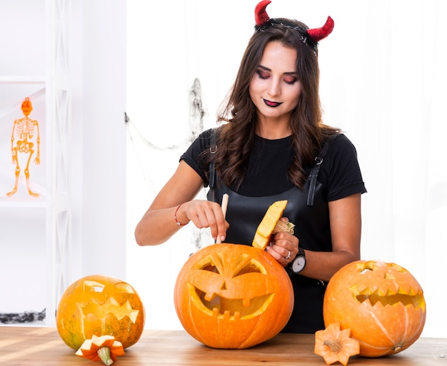 Adult woman carving pumpkins for halloween