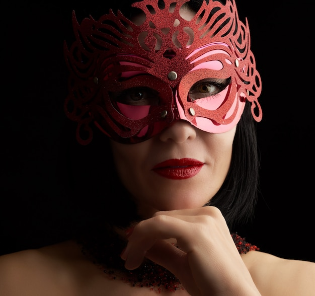 Adult woman of caucasian appearance with black hair wearing a red shiny carnival mask