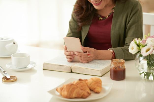 Взрослая женщина в чате с кем-то с помощью приложения messenger на своем смартфоне