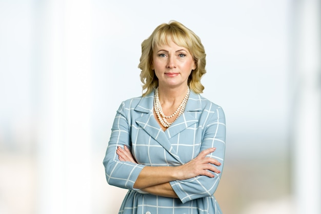 Adult woman corporate crossed arms portrait. beautiful mature blonde in light-blue checkered dress with crossed arms.