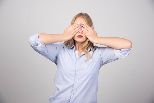Взрослая женщина закрыла глаза руками над серой стеной.