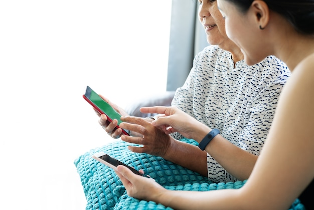 Adult woman and daughter using smartphone. woman point on mobile phone display