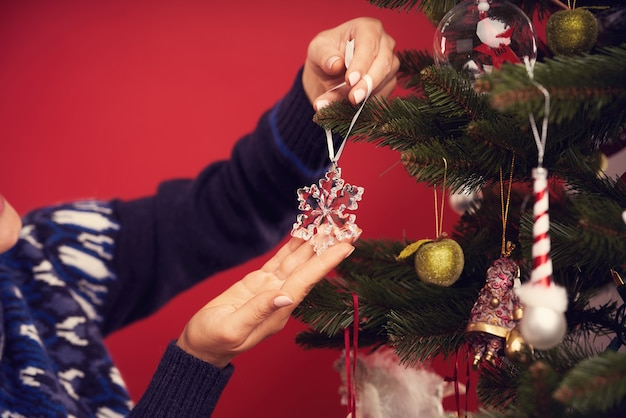 Adult woman decorating christmas tree over red background