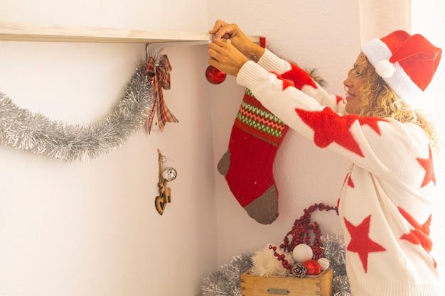 クリスマスのお祝いの休日のために家を飾る大人の女性