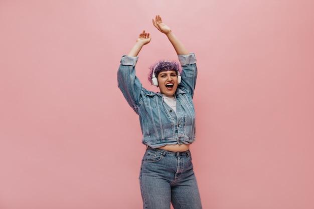 Donna adulta in jeans e giacca di jeans ascolta musica e canta canzoni. donna dai capelli corti in abito alla moda ballando.