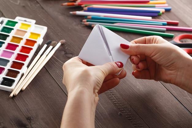 Взрослая женщина делает оригами лодка