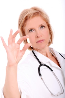 Adult woman doctor with pills in her hand over white background