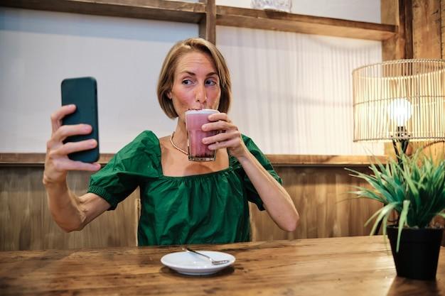 건강한 스무디를 마시면서 셀카를 찍는 성인 여성