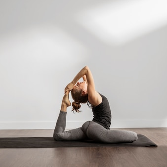 Adult woman doing yoga at home