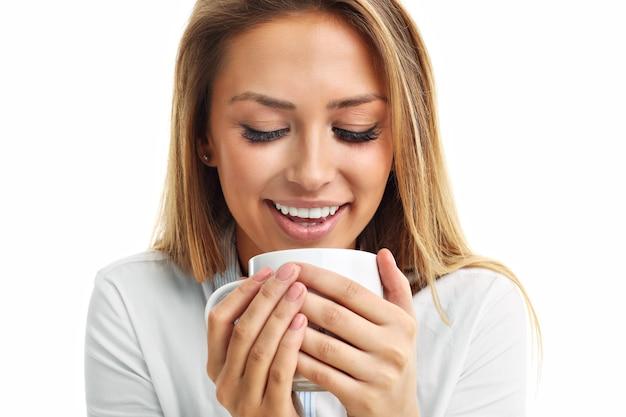 白で隔離のお茶のコーヒーを飲む大人の女性