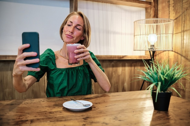 소셜 미디어 플랫폼을 위해 건강한 스무디를 마시는 성인 여성