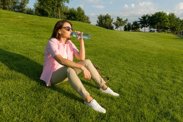 Adult woman drinks water from bottle