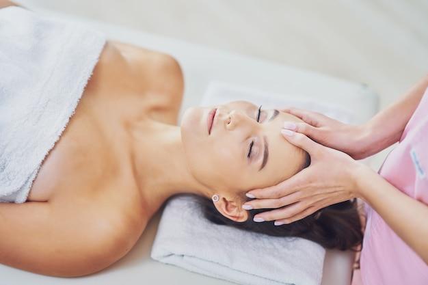 Взрослая женщина во время расслабляющего массажа в спа