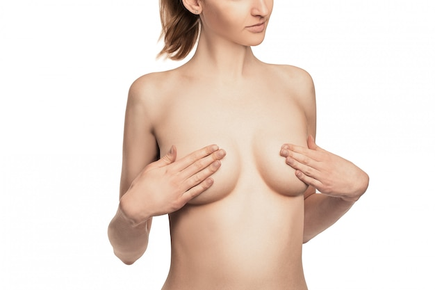 Adult woman examining breast for lumps, signs of breast cancer.