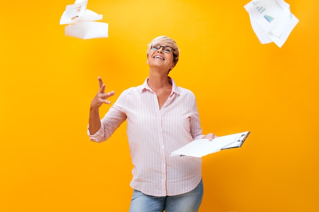 Adult woman in eyeglasses scatters paper sheets on orange background