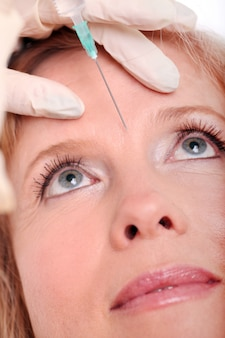 Adult woman having face injection