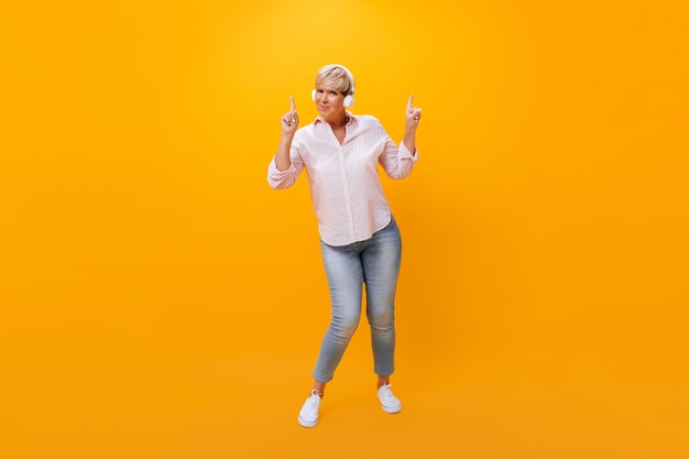Donna adulta in cuffie rivolte verso l'alto su sfondo arancione