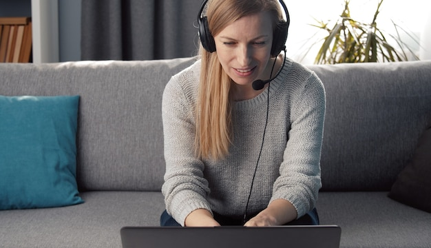 Adult woman in headset with mic sitting on couch at home looking at laptop screen talking to someone