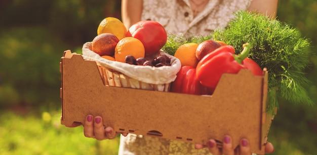 정원에서 신선한 새 시즌 수확 상자를 들고 성인 여자