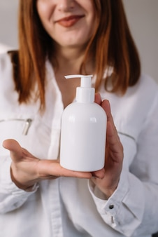Adult woman holding alcohol sanitizer gel or soap in hands