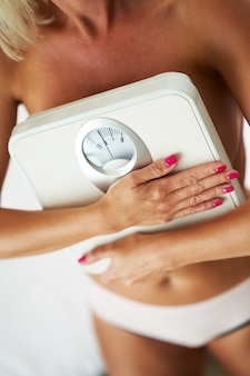 Adult woman holding scales in bathroom