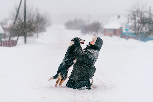 Adult woman hugging adorable dog on winter road outdoors.