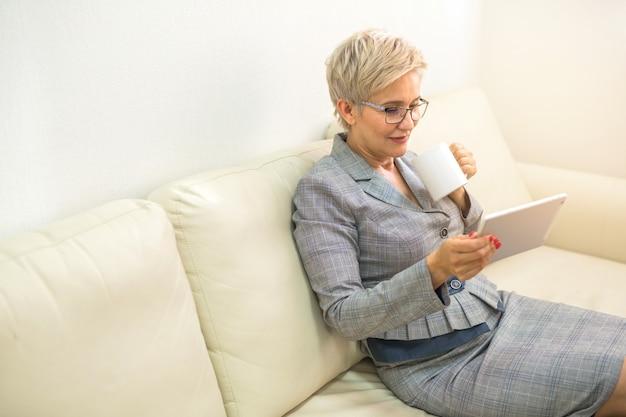 Взрослая женщина в костюме сидит на диване с планшетом и чашкой в руке