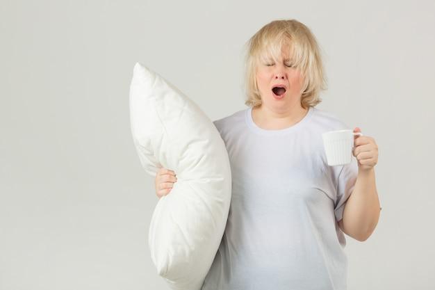 Взрослая женщина в белой футболке с подушкой