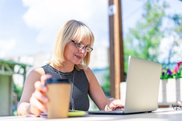 Взрослая женщина в очках с видеозвонком с ноутбуком на улице в парке, счастливый и улыбающийся старший
