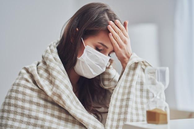Взрослая женщина в маске чувствует себя больной дома и смотрит на концепцию covid-19 в виде песочных часов Premium Фотографии