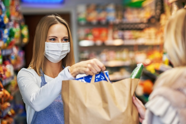 食料品店からオンライン注文を拾う医療マスクの大人の女性 Premium写真