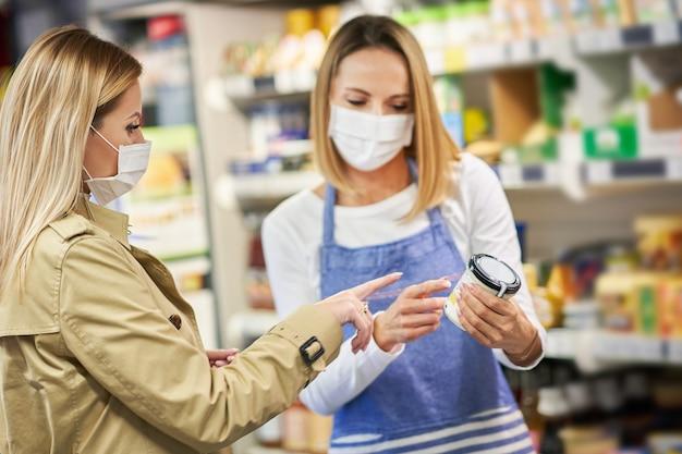 Взрослая женщина в медицинской маске покупает продукты