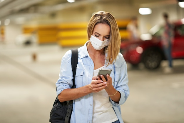 Взрослая женщина в защитной маске с помощью мобильного телефона на подземной автостоянке