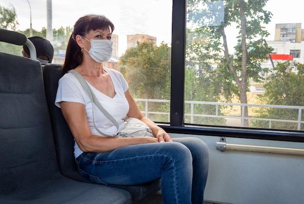 防護マスクの大人の女性は、市内の公共交通機関で空に一人で乗ります。社会的距離。バスの乗客