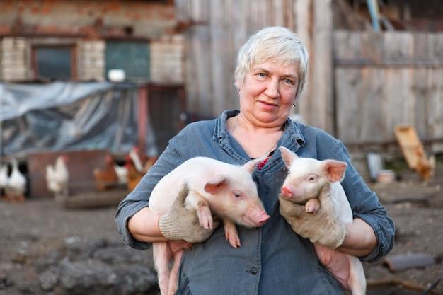 Взрослая женщина держит в руках двух поросят. животноводство