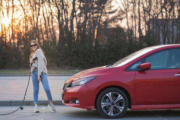 大人の女性が楽しんでカメラを見て、充電ステーションで電気自動車の近くに立って電源ケーブル供給を手で押し