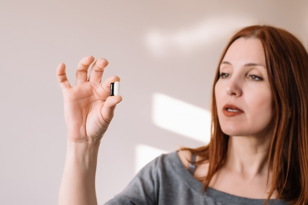 Adult woman looking at black and white pills