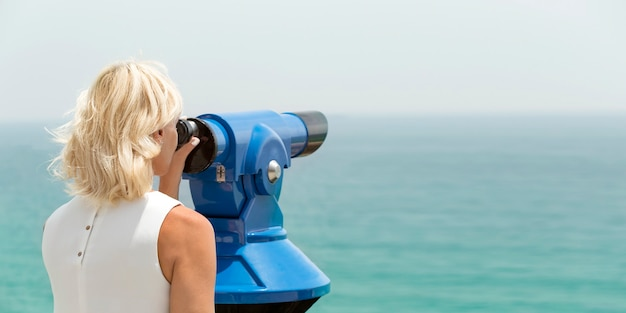 Adult woman looking through binocular viewer on the sea landscape