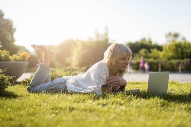 Взрослая женщина смотрит на ноутбук, лежа на траве снаружи в парке.