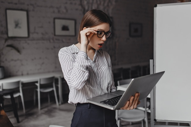 Adult woman looks at laptop in shock, taking off her glasses in surprise. portrait of employee in black and white outfit in office.