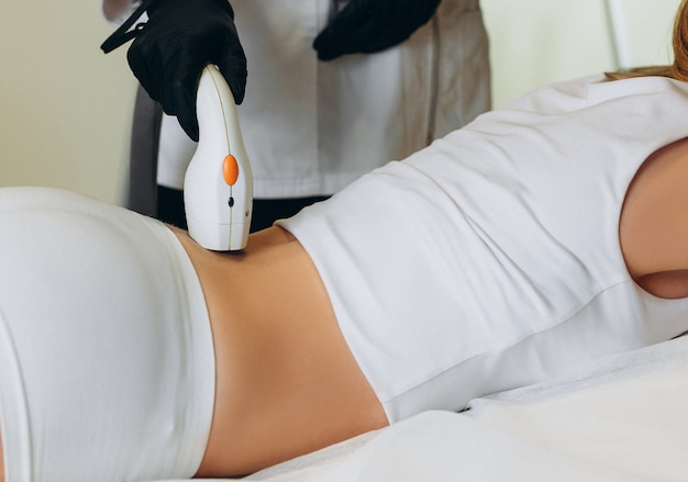 Adult woman lying on medical table in beauty clinic, having laser hair removal in professional beauty salon. female cosmetician in uniform using machine for laser hair removal.