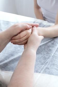 Взрослая женщина-массажист массирует женские пальцы, чтобы они расслабились после спа-процедур.