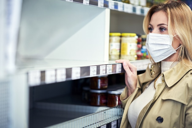 Adult woman in medical mask in front of empty shelves in grocery store