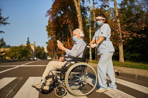 도시에서 노인과 함께 걷는 성인 여성 의료 종사자