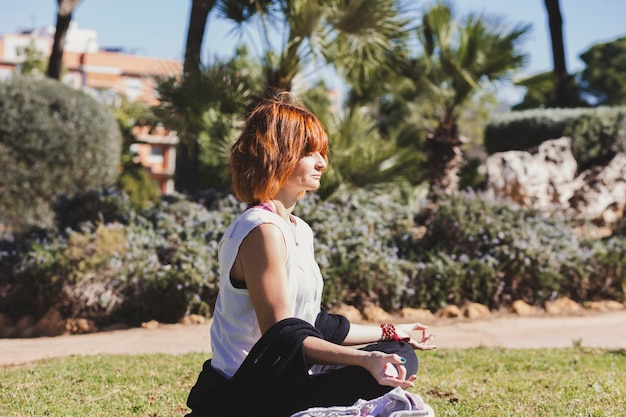 Adult woman meditating in park