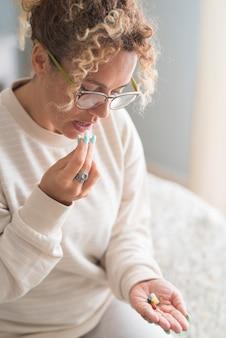 大人の女性が自宅で薬を服用し、一人でベッドに座る病気と健康問題女性の成熟した女性が健康状態に気を配っている