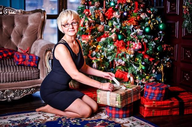크리스마스 밤에 성인 여자 실내 집에서 카펫 바닥에 앉아 선물을 풀고.