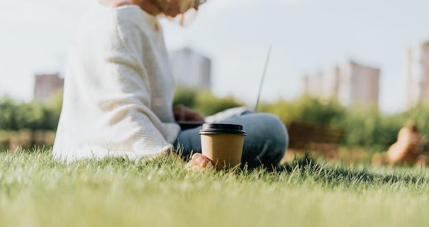 Взрослая женщина на траве с ноутбуком
