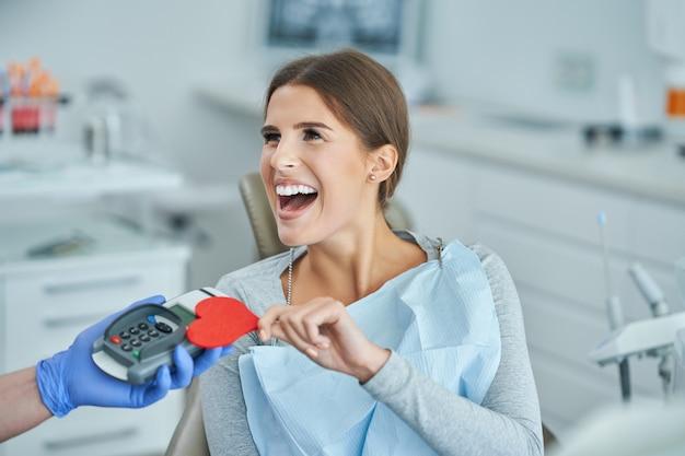 歯科医院への訪問のために支払う大人の女性