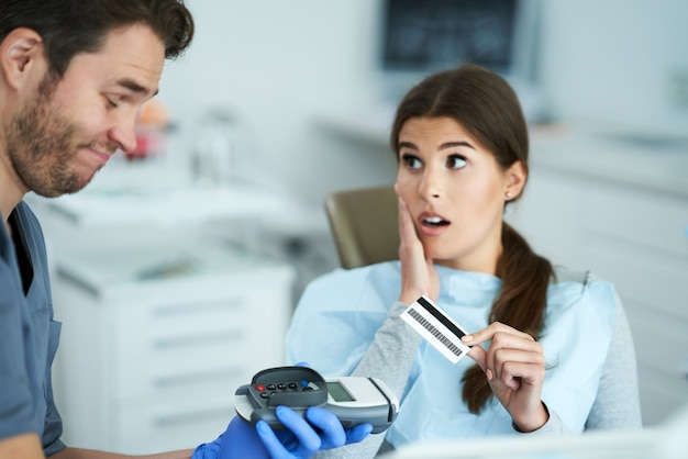 Adult woman paying for visit in dentist office